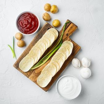 Conjunto de batatas fritas crocantes, com molho de tomate e creme de leite, na superfície de pedra branca