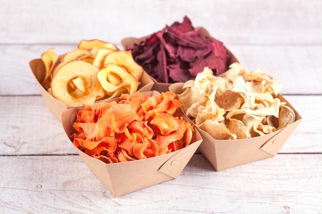 Conjunto de batatas fritas de legumes e frutas em tigelas de artesanato. frutas e legumes secos. um lanche orgânico para toda a família. conceito de alimentação saudável