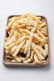 Conjunto de batatas fritas em fatias de forno congelado, na bandeja de madeira, na mesa branca