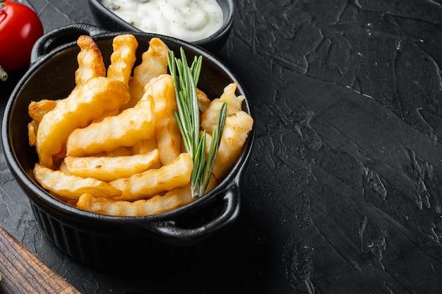 Conjunto de batatas fritas saborosas com ervas, na mesa preta
