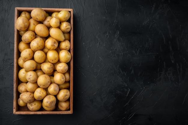 Conjunto de batatas novas cruas, em caixa de madeira, na mesa de pedra preta, vista de cima plana