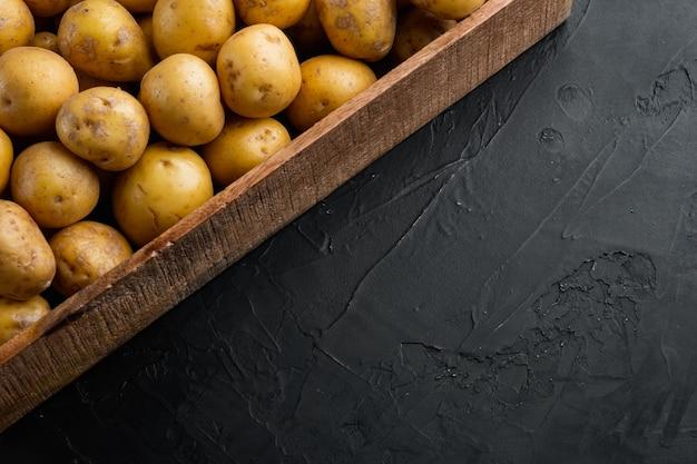 Conjunto de batatinhas frescas com casca, em caixa de madeira, sobre mesa de pedra preta