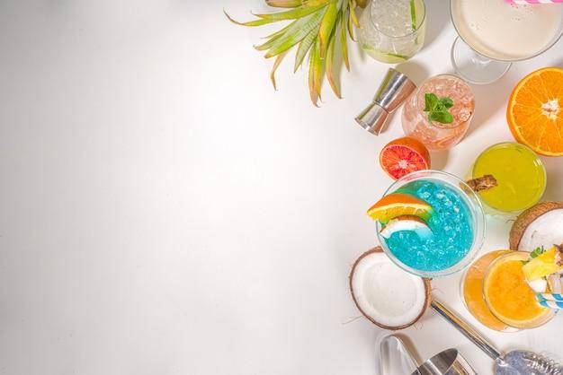 Conjunto de bebidas coloridas de verão. vários coquetéis e bebidas alcoólicas brilhantes, em copos diferentes, com frutas tropicais