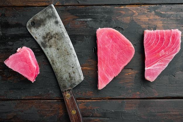 Conjunto de bife de atum cru e velha faca de cutelo de açougueiro na velha mesa de madeira escura, vista de cima plana