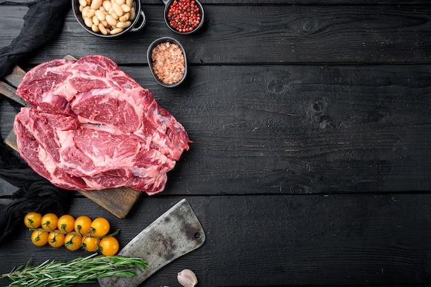 Conjunto de bife de bife alimentado com grama crua com sal e pimenta e ervas, e uma velha faca de cutelo de açougueiro, na mesa de madeira preta