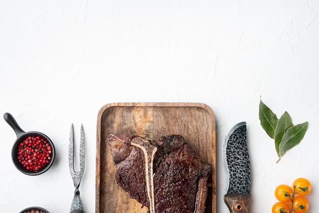 Conjunto de bife de carne assada ou de carne bovina porterhouse, em bandeja de madeira, vista de cima plana, com espaço de cópia para o texto
