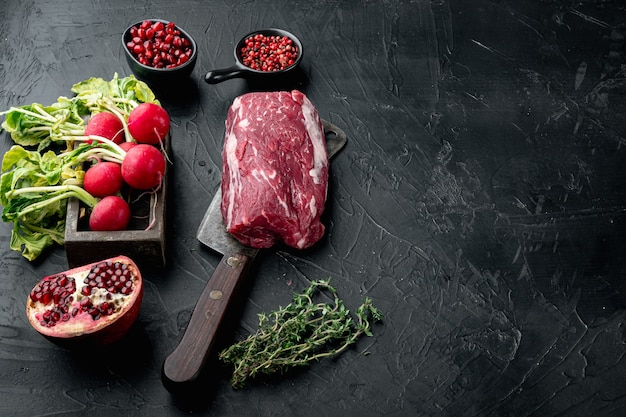 Conjunto de bife de carne bovina de carne crua de conceito de comida orgânica, filé mignon cortado, na mesa de pedra preta