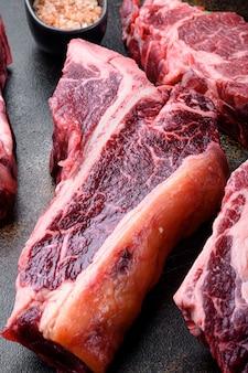 Conjunto de bife de carne bovina ou osso cru envelhecido a seco, sobre fundo rústico escuro antigo