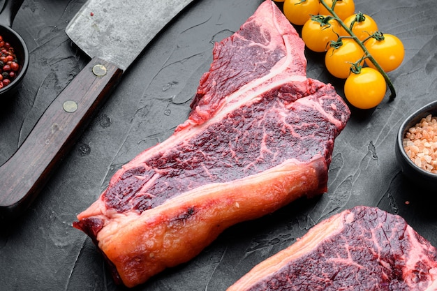 Conjunto de bife de carne crua maturada a seco ou carne bovina porterhouse, sobre fundo de pedra preta