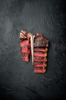 Conjunto de bife de carne grelhado ao ponto médio fatiado, osso t ou corte porterhouse, em mesa de pedra preta, vista superior plana