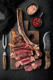 Conjunto de bife de tomahawk grelhado em fatias, em uma tábua de servir de madeira, em uma mesa de pedra preta, vista de cima plana
