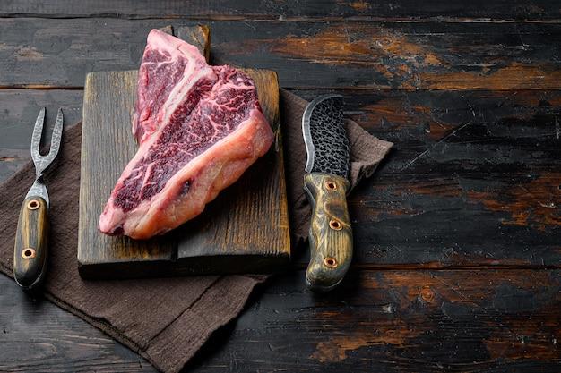Conjunto de bife t-bone de carne crua fresca seca envelhecida, numa tábua de madeira, no fundo da mesa de madeira escura velha, com espaço de cópia para o texto