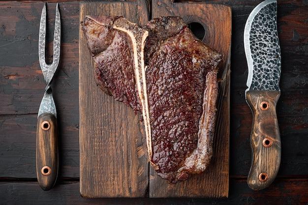 Conjunto de bife t bone grelhado, em tábua de servir de madeira, vista de cima plano