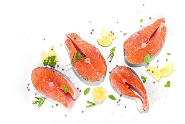 Conjunto de bifes de salmão crus frescos prontos para cozinhar, fatias de peixe vermelho em porções com sal e especiarias, no espaço de cópia da vista superior do fundo da mesa branca