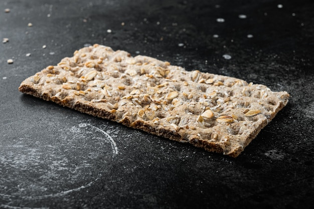 Conjunto de biscoitos crocantes de centeio fino, em mesa de pedra preta escura