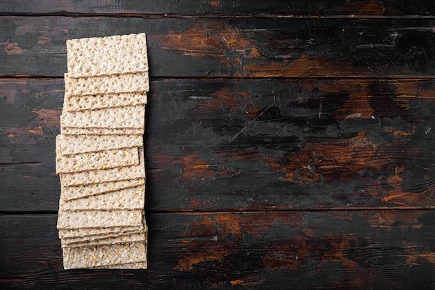 Conjunto de biscoitos crocantes de centeio fino, em mesa velha de madeira escura