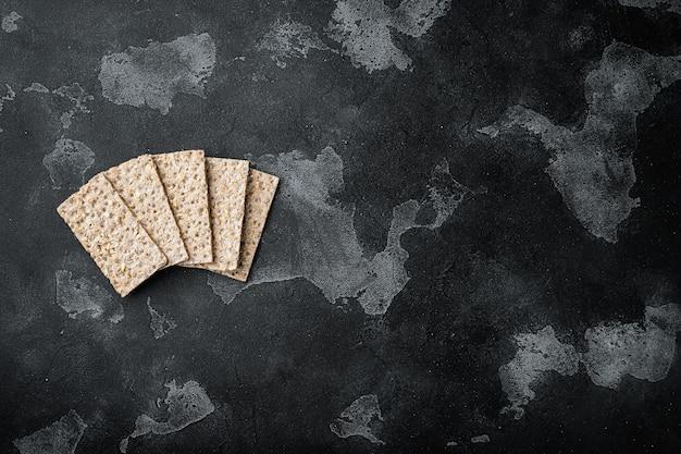 Conjunto de biscoitos de centeio integral integral, em mesa de pedra preta escura, vista de cima plano