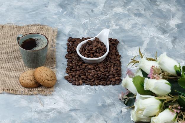 Conjunto de biscoitos, xícara de café, flores e grãos de café em uma jarra de porcelana branca sobre fundo de mármore azul. fechar-se.