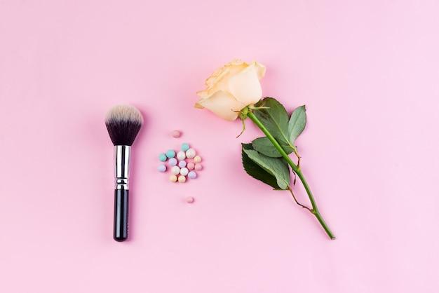 Conjunto de bolas de pó de cosméticos coloridos e escova com rosa sobre fundo rosa.