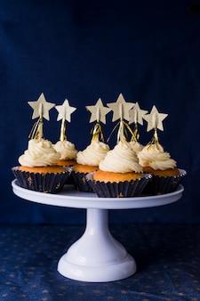 Conjunto de bolos saborosos com creme de manteiga e estrelas em stand