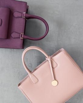 Conjunto de bolsas femininas da moda em superfície gessada cinza, vista superior
