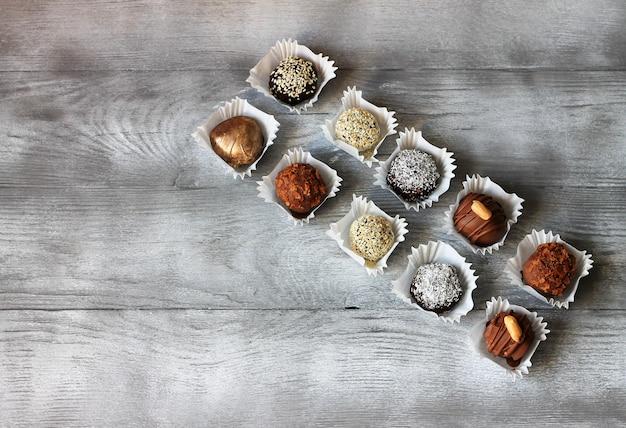 Conjunto de bombons de chocolate. bombons artesanais exclusivos na mesa de madeira. vista superior, copyspace