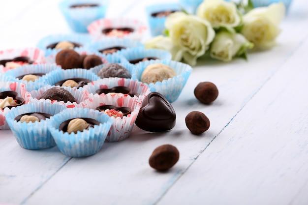 Conjunto de bombons de chocolate com flores sobre fundo claro de madeira, close-up
