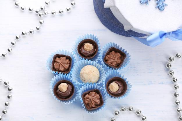 Conjunto de bombons de chocolate em um fundo claro de madeira