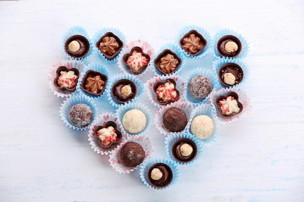 Conjunto de bombons de chocolate formando um coração em uma luz de madeira