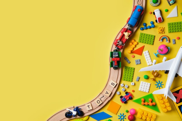 Conjunto de brinquedos infantis diferentes, ferrovia de madeira, trem, construtor em uma superfície amarela