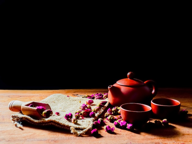 Conjunto de bule e xícara de chá com folhas de chá rosa na mesa de madeira e fundo preto