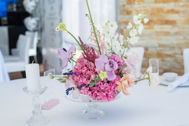 Conjunto de buquê de close up de rosas frescas, astilbe, cravo, delphinium, eustoma, ornithogalum, lavanda e hortênsia em banquete de casamento