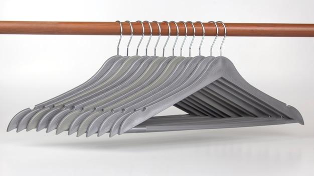 Conjunto de cabides cinza em um espaço em branco. artigos para guardar roupas.
