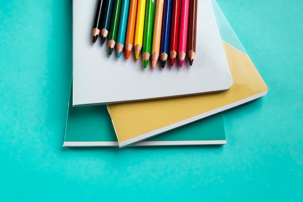 Conjunto de cadernos e lápis de cor verde com espaço para texto.
