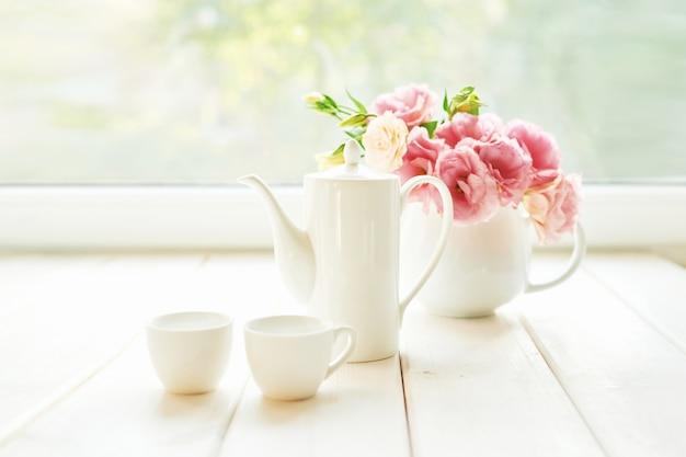 Conjunto de café ao lado de um vaso de flores em uma mesa contra uma janela