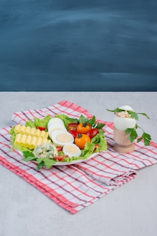 Conjunto de café da manhã de legumes, ovos cozidos e fatias de manteiga em uma travessa sobre uma toalha na mesa de mármore.