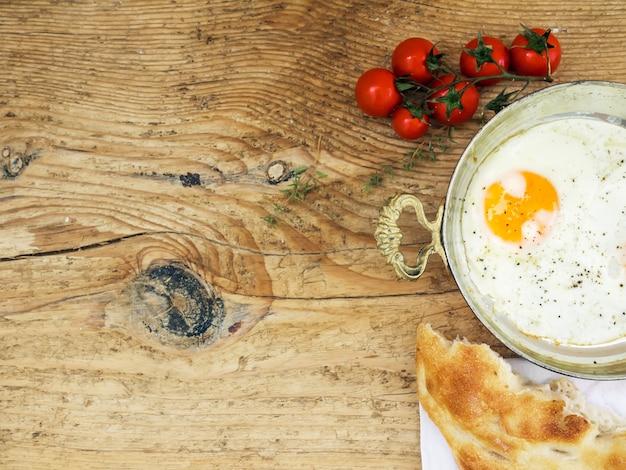 Conjunto de café da manhã: ovo frito, pão e tomate cereja em uma mesa de madeira