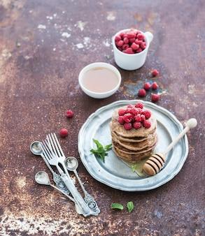 Conjunto de café da manhã. panquecas de trigo sarraceno com framboesas frescas, mel e folhas de hortelã sobre metal grunge