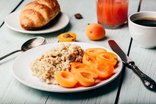 Conjunto de café da manhã. papa de aveia com damasco fatiado, xícara de café, copo de suco de toranja e croissant