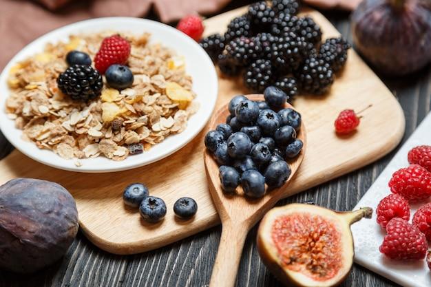 Conjunto de café da manhã saudável, muesli e frutas no escuro rústico