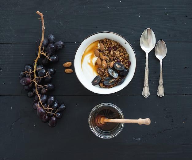 Conjunto de café da manhã saudável. tigelas de granola de aveia com iogurte, uvas frescas, amêndoa e mel sobre a superfície de madeira preta