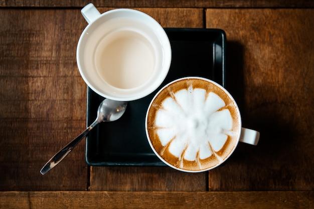 Conjunto de café expresso quente inclui chá e açúcar no fundo da mesa