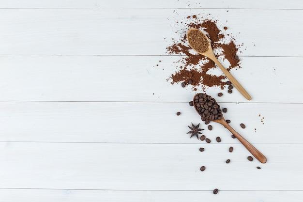 Conjunto de café moído e grãos de café em uma colher de pau em um fundo de madeira. colocação plana.