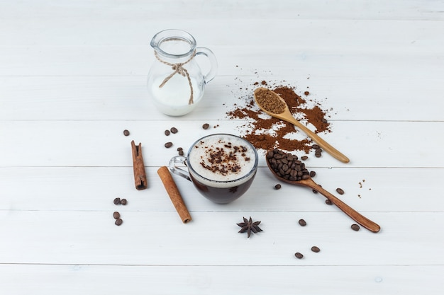 Conjunto de café moído, grãos de café, paus de canela, leite e café em uma xícara com fundo de madeira. vista de alto ângulo.