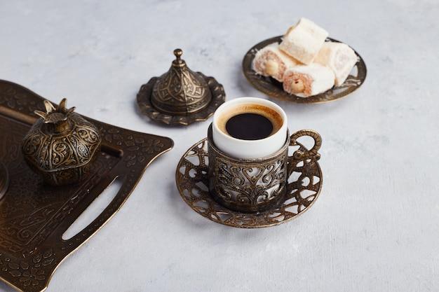 Conjunto de café turco servido com lokum em travessa metálica.