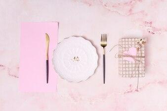 Conjunto de caixa de presente perto de prato, papel e talheres