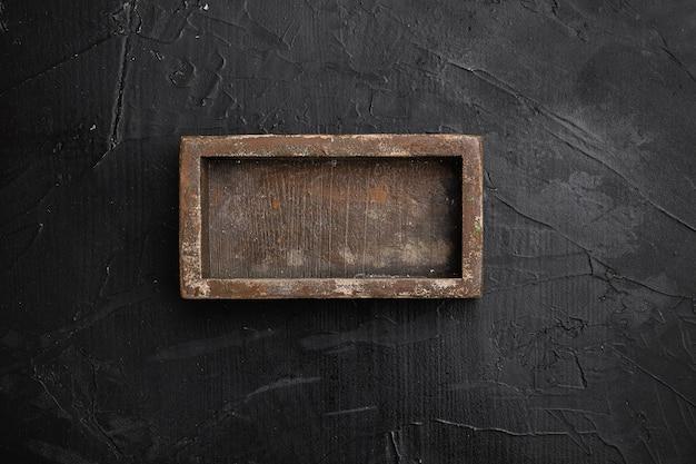 Conjunto de caixa ou recipiente de madeira rústica com espaço de cópia para texto ou comida, vista de cima plana, sobre fundo preto de mesa de pedra escura