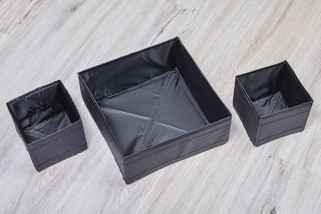 Conjunto de caixas de arrumação dobráveis em tecido preto.