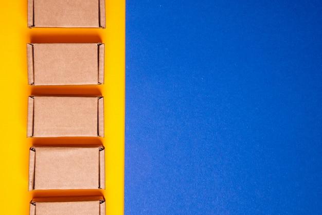 Conjunto de caixas de papelão no fundo amarelo azul