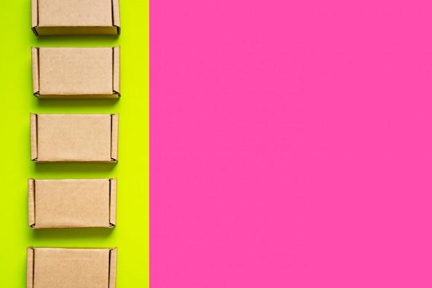 Conjunto de caixas de papelão sobre fundo verde, rosa